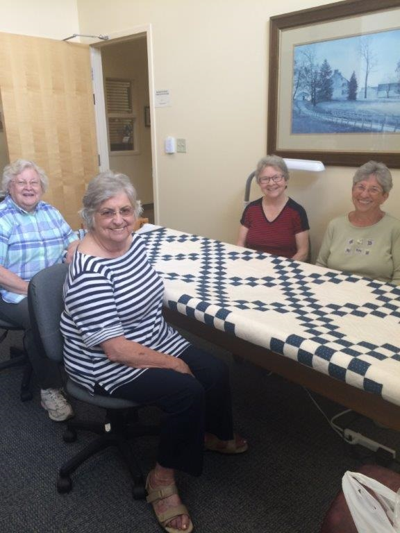 Ladies quilting together.