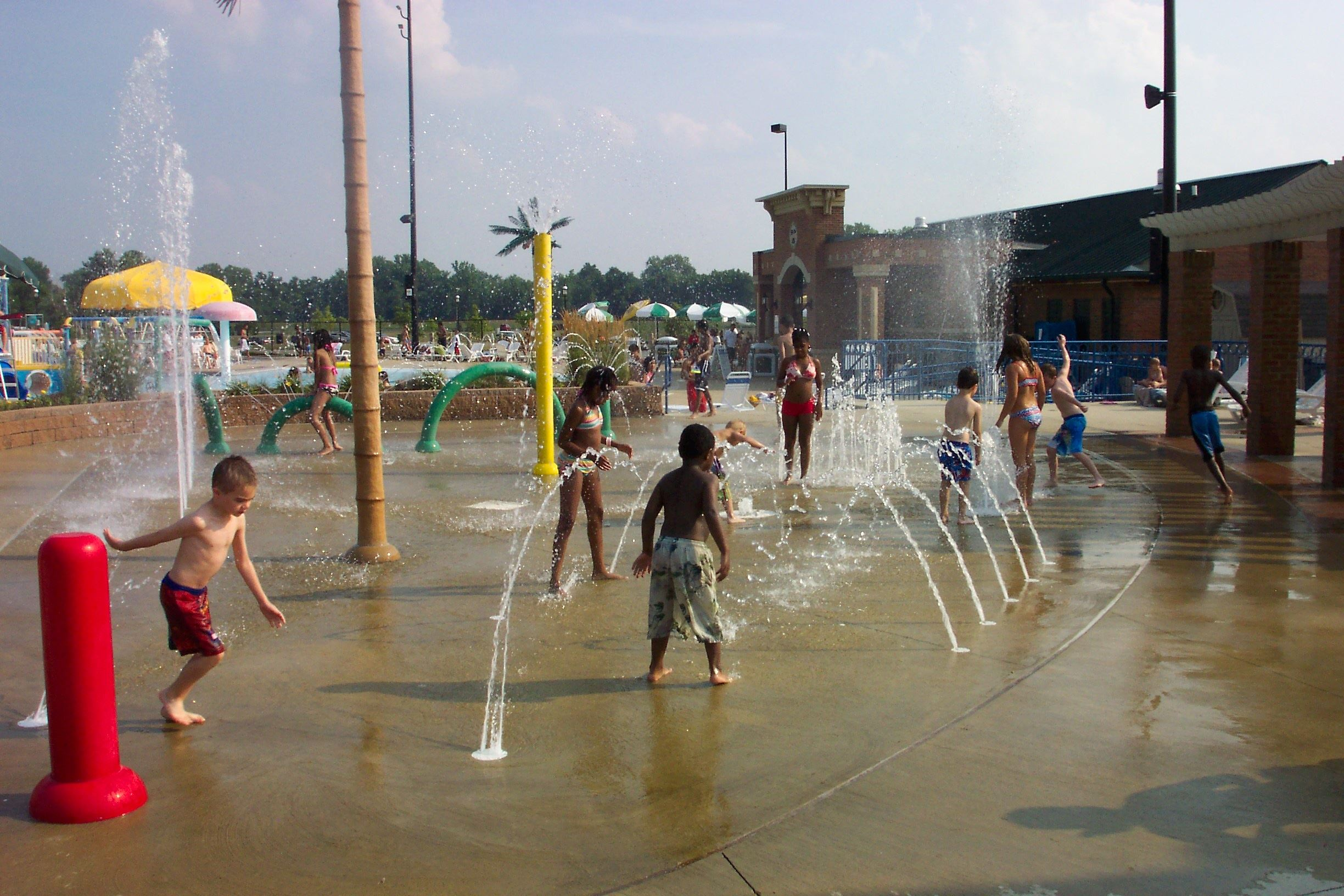 "Children playing in the ""sprayground"" area of the outdoor pool."