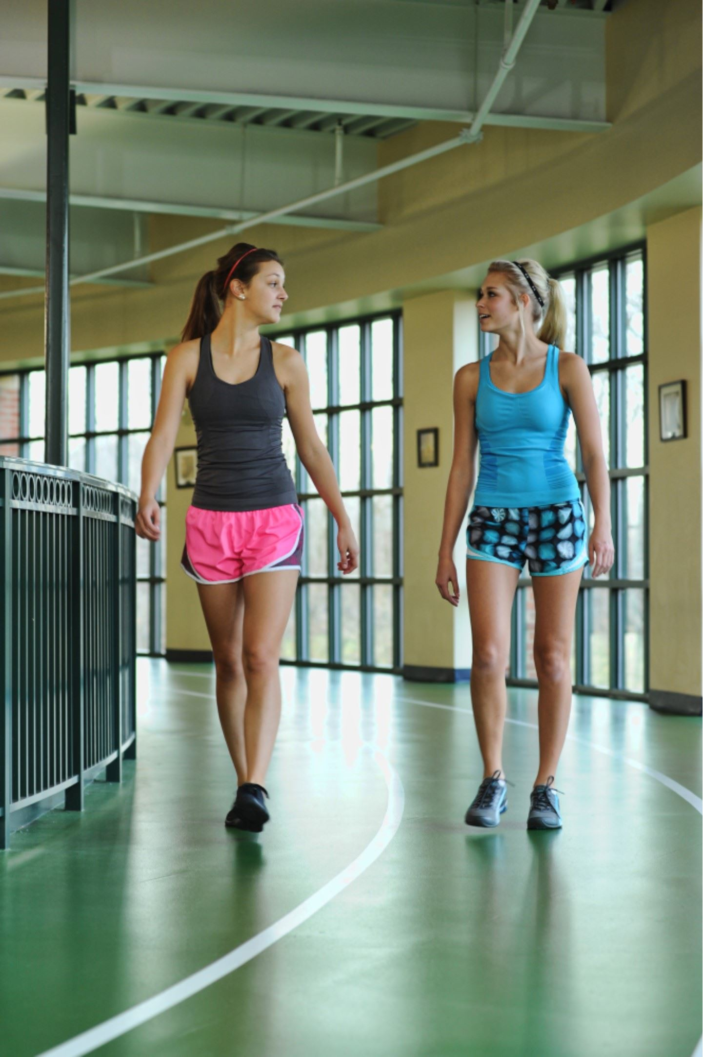 Two women walking on the indoor track.