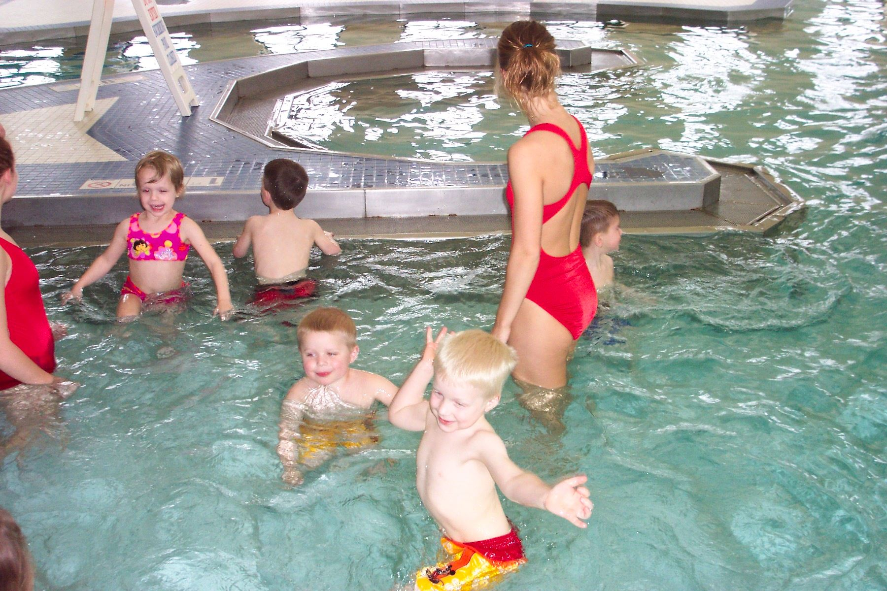 A group of supervised children enjoying themselves in the indoor pool.