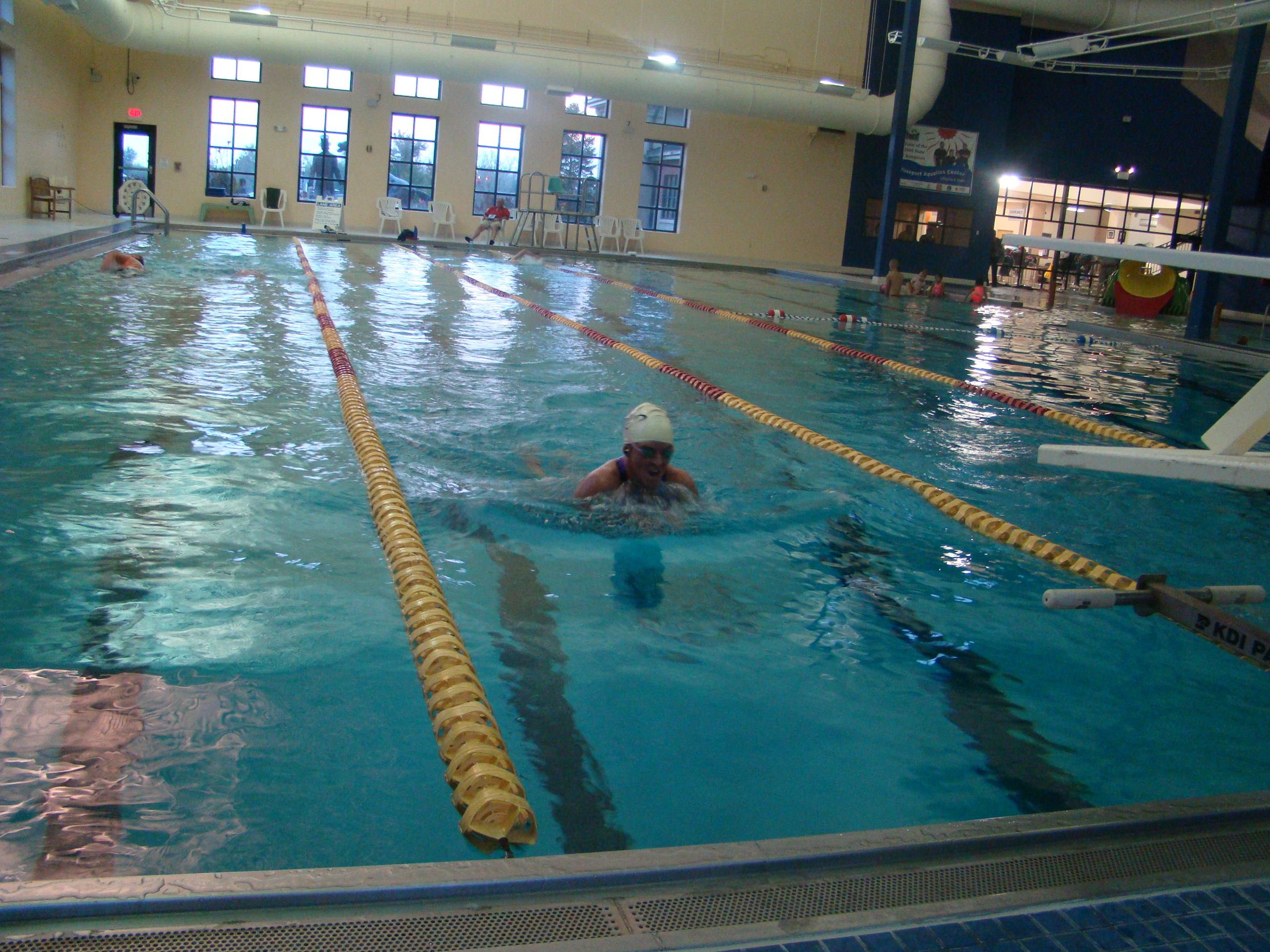 A swimmer swimming laps in a lane at the indoor pool.