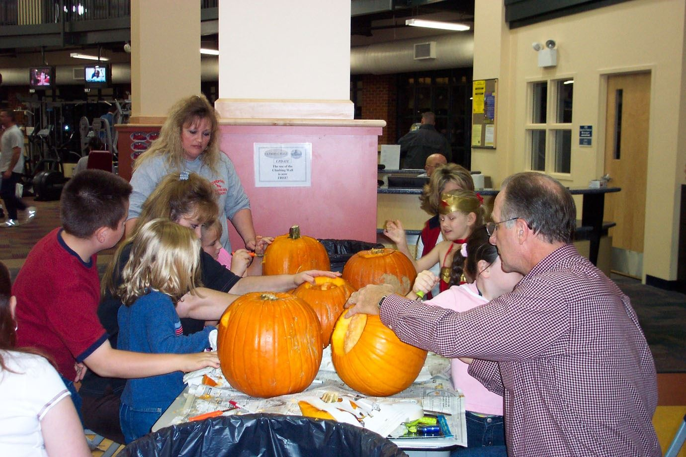 Adults and kids carving pumpkins together.