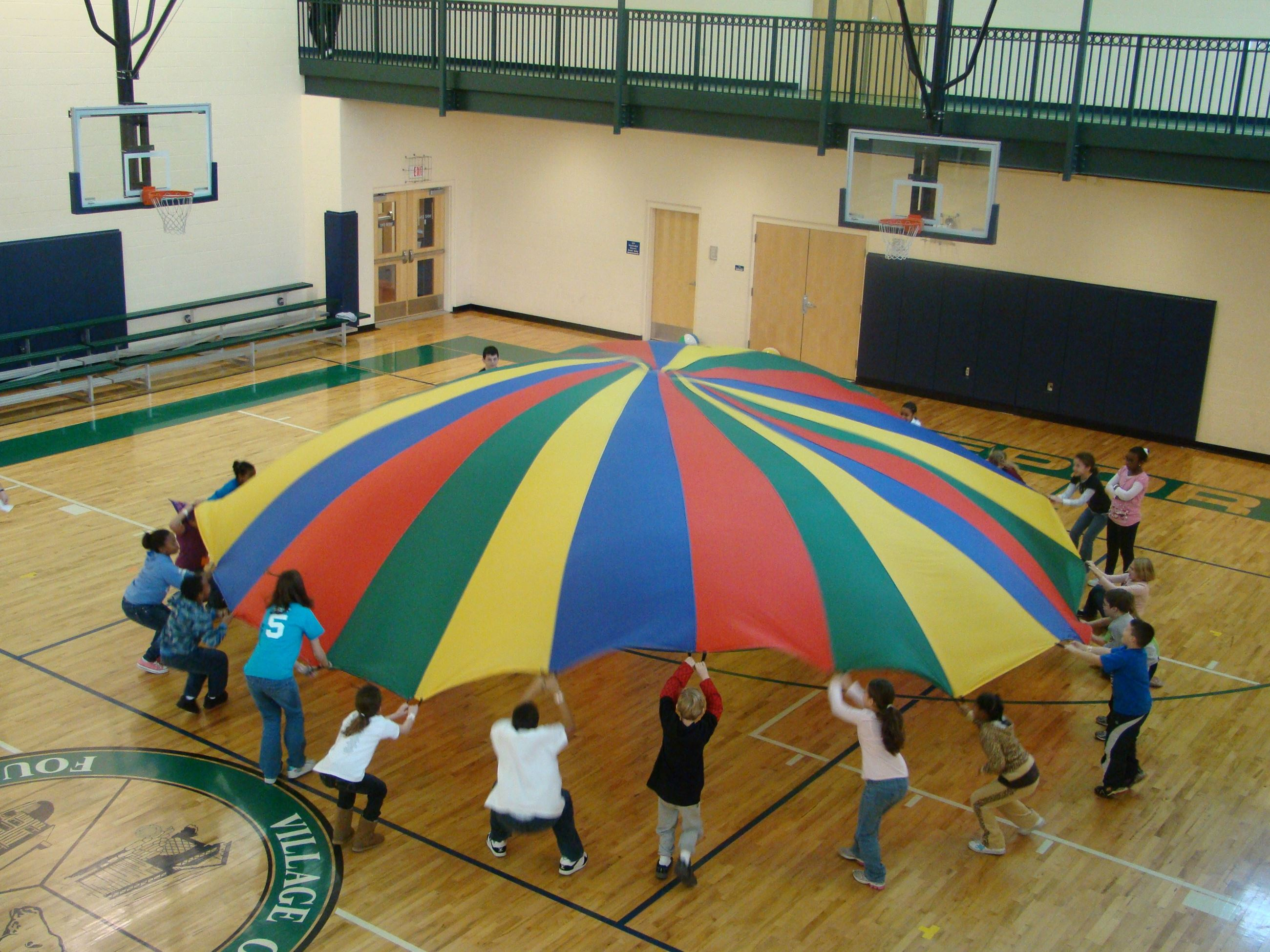 Kids playing with a parachute in the Recreation Center gymnasium.